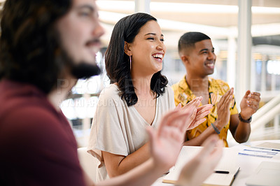 Buy stock photo Shot of a young businesswoman applauding while sitting alongside her colleagues during a presentation in an office