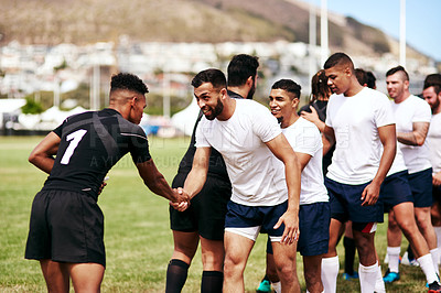 Buy stock photo Shot of a group of young men shaking hands during a game of rugby