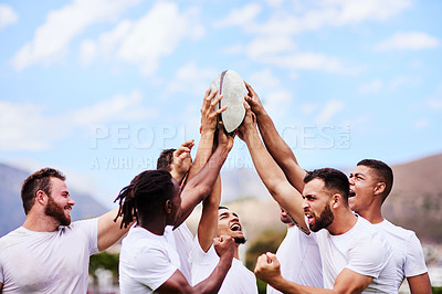 Buy stock photo Shot of a group of young rugby players raising a rugby ball in solidarity at a game