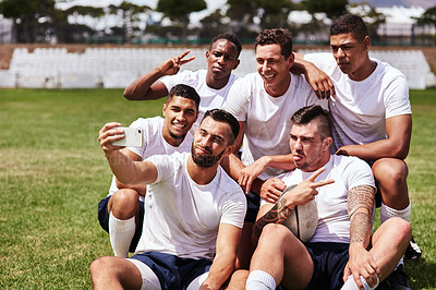Buy stock photo Shot of a young man taking a selfie with his team mates at a rugby game