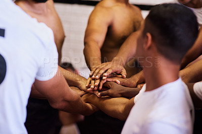 Buy stock photo Shot of a group of young rugby players joining their hands in solidarity in the locker room