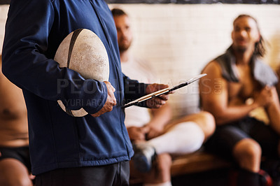 Buy stock photo Cropped shot of a rugby coach addressing his team players in a locker room