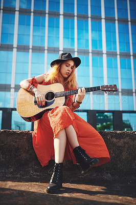 Buy stock photo Shot of a beautiful young woman playing the guitar while out in the city