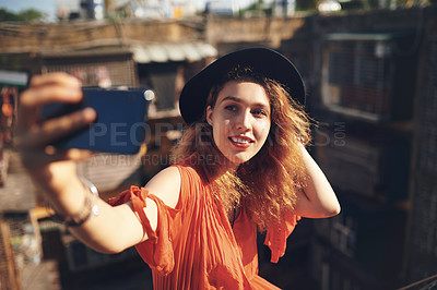 Buy stock photo Cropped shot of a beautiful young woman taking selfies while out in the city
