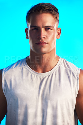 Buy stock photo Studio portrait of a handsome young male athlete posing against a blue background