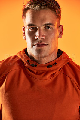 Buy stock photo Studio portrait of a handsome young male athlete posing against an orange background