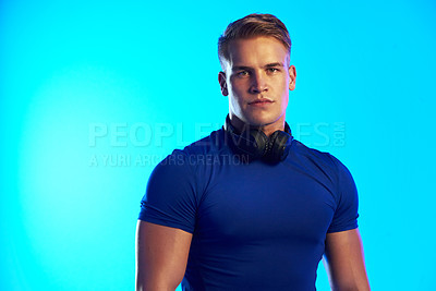 Buy stock photo Studio portrait of a handsome young male athlete posing with headphones around his neck against a blue background