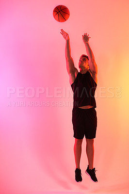 Buy stock photo Studio shot of a handsome young male basketball player taking a jump shot against a multi-coloured background
