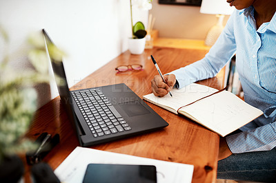 Buy stock photo Cropped shot of a businesswoman writing financial data in a notebook at her desk