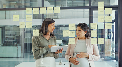Buy stock photo Shot of two businesswomen using a digital tablet during a brainstorming session