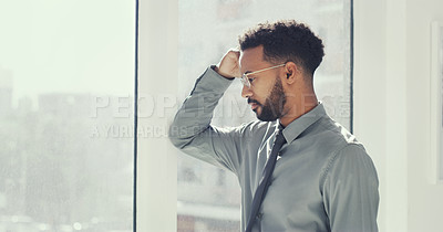 Buy stock photo Cropped shot of a young businessman looking worried while standing in his office