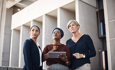Buy stock photo Shot of a group of businesswomen using a digital tablet together against a city background