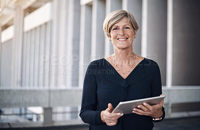 Buy stock photo Shot of a mature businesswoman using a digital tablet against a city background