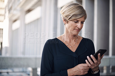 Buy stock photo Shot of a mature businesswoman using a smartphone against a city background