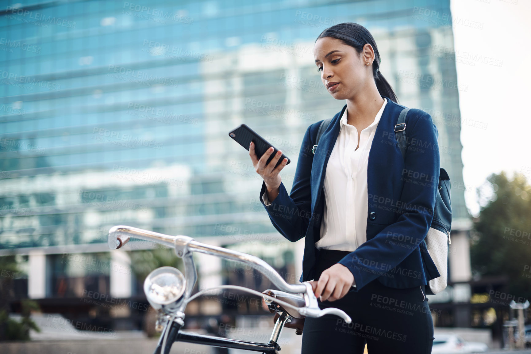 Buy stock photo Shot of a young businesswoman using a smartphone while traveling with a bicycle through the city