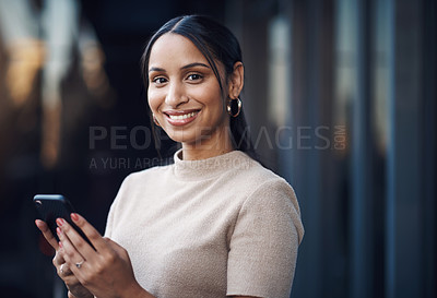 Buy stock photo Cropped portrait of an attractive young businesswoman sending a text while working in her office