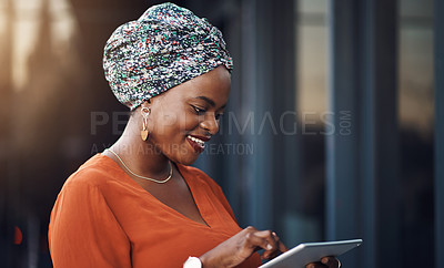 Buy stock photo Cropped shot of an attractive businesswoman using her tablet while standing in the office