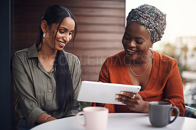 Buy stock photo Cropped shot of two attractive businesswomen working on a tablet together in their office