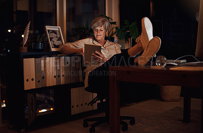 Buy stock photo Full length shot of an attractive mature businesswoman looking relaxed while using her tablet late at night in the office
