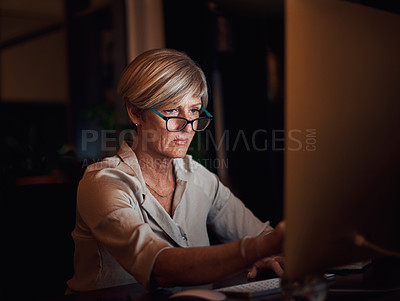 Buy stock photo Cropped shot of an attractive mature businesswoman working on her computer late at night in the office