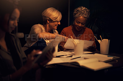 Buy stock photo Shot of two businesswomen going through paperwork together in an office at night