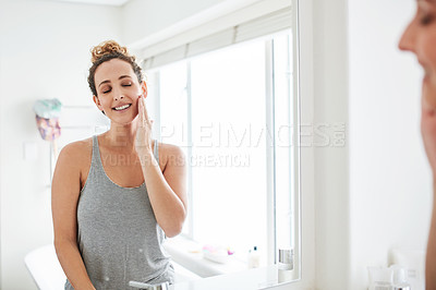 Buy stock photo Shot of a young woman feeling her smooth skin in front of the bathroom mirror