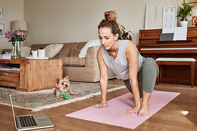 Buy stock photo Shot of a young woman using a laptop while doing yoga at home