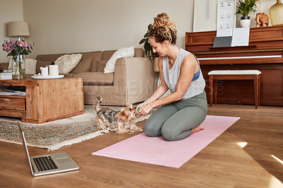 Buy stock photo Shot of a young woman playing with her dog while practicing a yoga routine at home