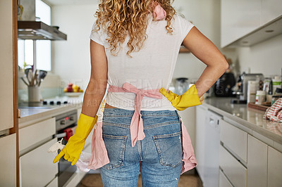 Buy stock photo Rearview shot of a young woman cleaning her kitchen at home