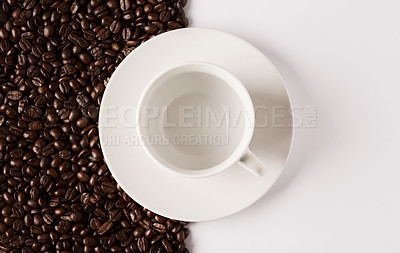 Buy stock photo Closeup shot of an empty cup and saucer against a half-and-half background of coffee beans