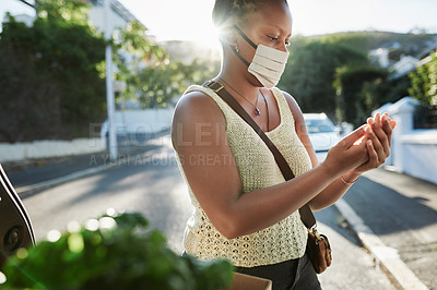 Buy stock photo Shot of a young woman wearing a mask and sanitising her hands after shopping for groceries