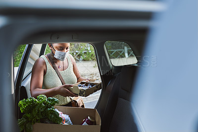 Buy stock photo Shot of a young woman wearing a mask and packing groceries into her car