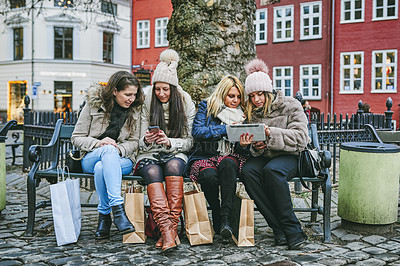 Buy stock photo Shot of a group of young women using their smartphones while out shopping in the city
