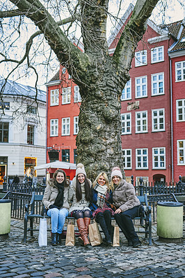 Buy stock photo Portrait of a group of young women taking a break while shopping in the city