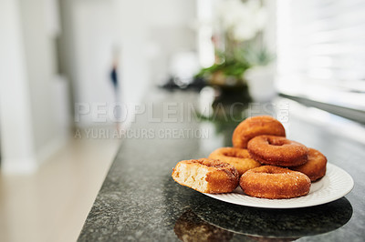 Buy stock photo Shot of a plate of donuts in a kitchen
