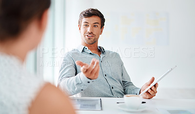 Buy stock photo Shot of a young businessman having a discussion with a woman in an office
