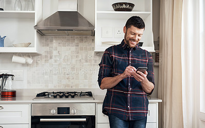 Buy stock photo Shot of a young man using a smartphone in his kitchen at home