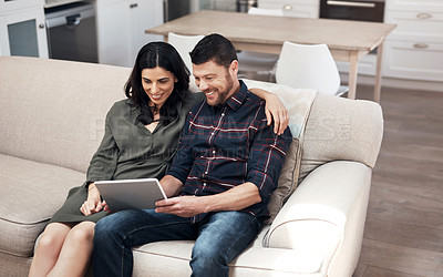 Buy stock photo Shot of a young couple using a digital tablet together on the sofa at home