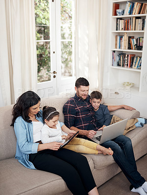 Buy stock photo Shot of a young family using their wireless devices on the sofa at home