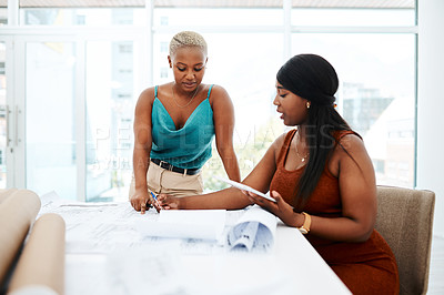 Buy stock photo Shot of two young women going over blueprints in a modern office