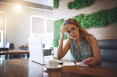 Buy stock photo Shot of a young woman using a laptop and looking stressed while working at a cafe