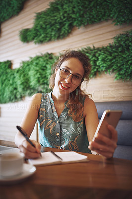 Buy stock photo Shot of a young woman using a smartphone while working at a cafe