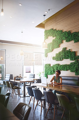 Buy stock photo Shot of a young woman using a laptop and writing in a notebook while working at a cafe