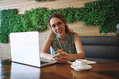 Buy stock photo Shot of a young woman using a laptop while working at a cafe