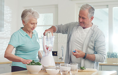 Buy stock photo Cropped shot of a senior couple making a healthy smoothie together at home