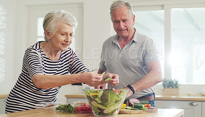 Buy stock photo Cropped shot of a happy senior couple preparing a salad together at home