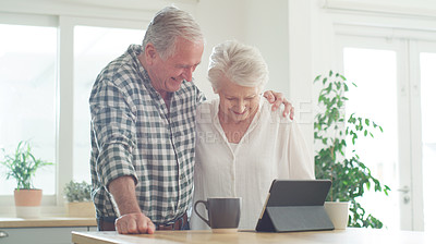 Buy stock photo Cropped shot of a senior couple looking at something on a digital tablet together