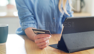 Buy stock photo Cropped shot of a woman holding her credit card while browsing on her digital tablet