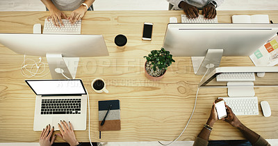 Buy stock photo High angle shot of a group of unrecognisable businesspeople working on computers in an office