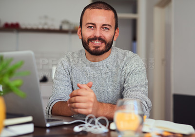 Buy stock photo Portrait of a young man working on a laptop at home